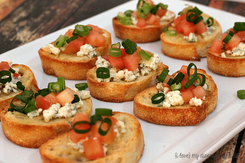 Creamy blue cheese crumbles and ripe tomatoes on a warm toasted baguette