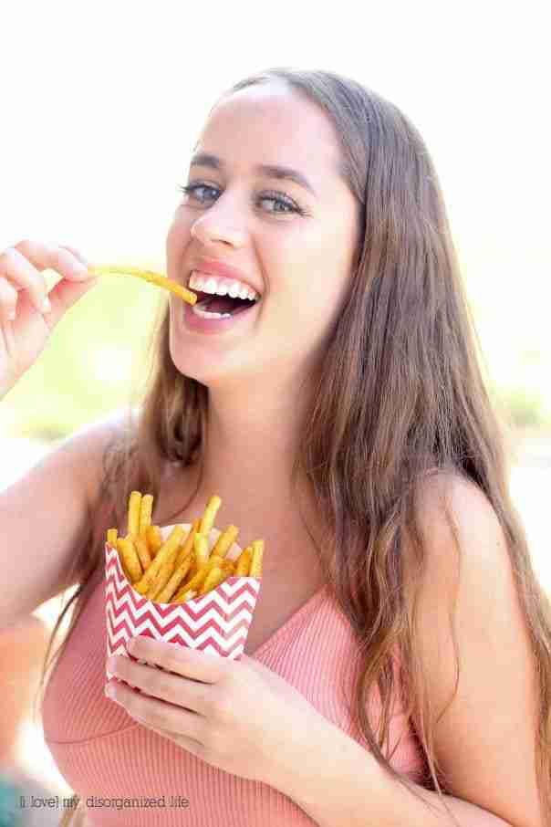 Woman eating french fries with homemade cajun seasoning recipe