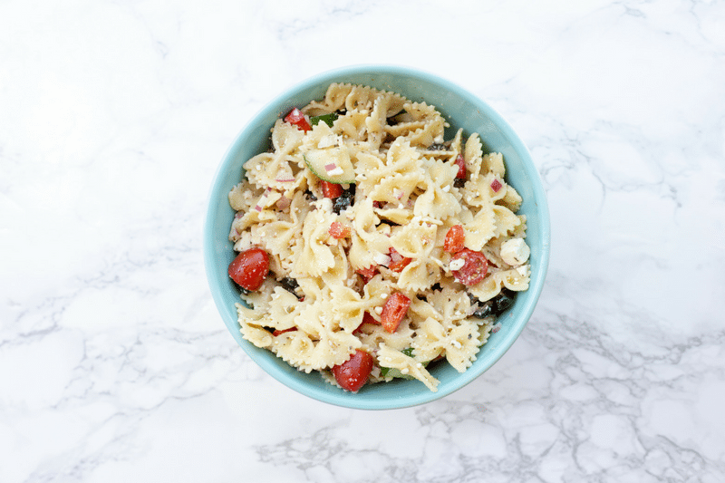 Greek pasta salad in blue bowl on white marble counter