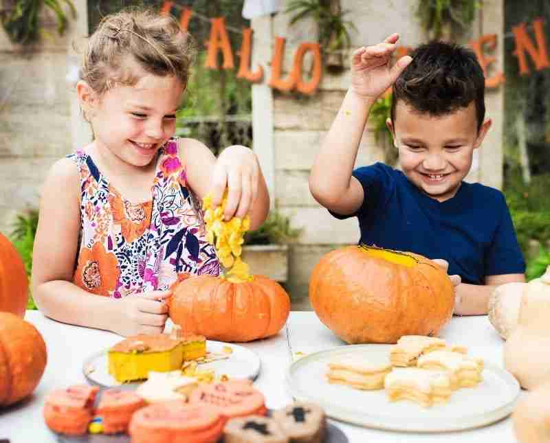 Boy and girl scooping insides out of pumpkins