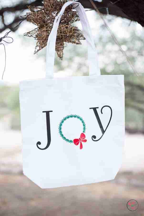 Joy tote hanging from a tree in front of natural vine hanging star