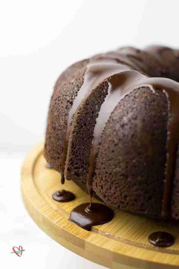Close up of whole coconut fudge cake on cake plate