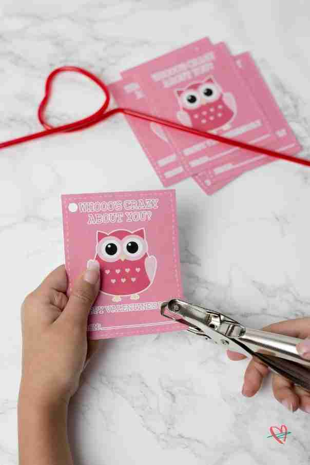 Girl punching holes in kid's Valentine's Day cards using hole punch