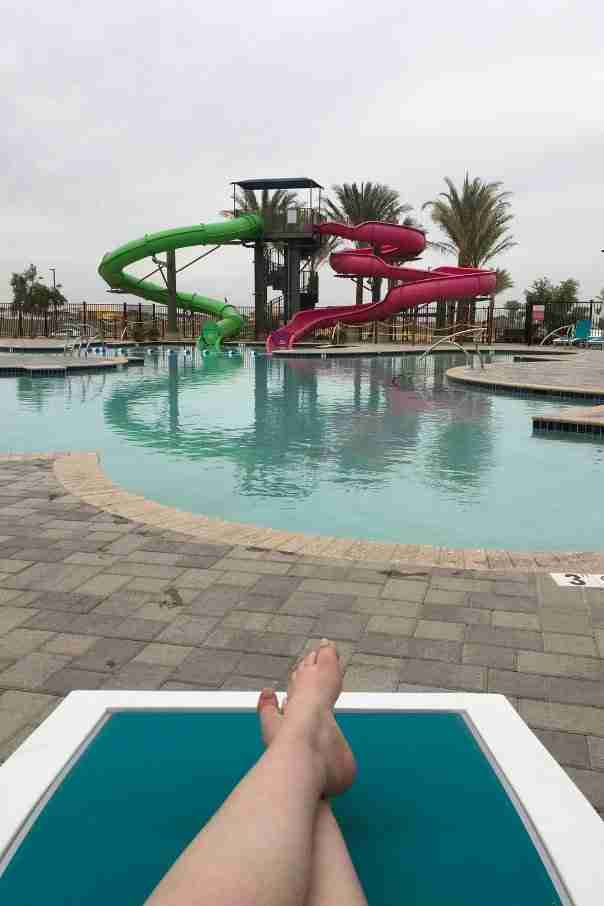 Woman laying by the pool facing water slides