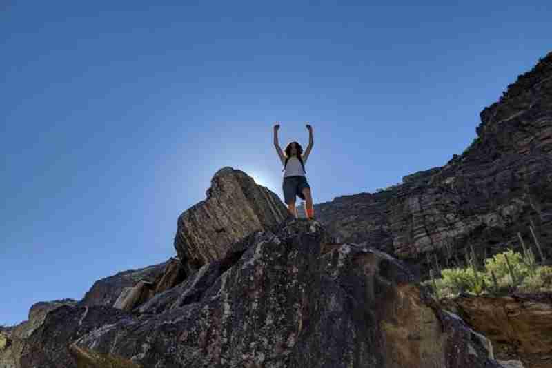 Man on top of big rock hiking