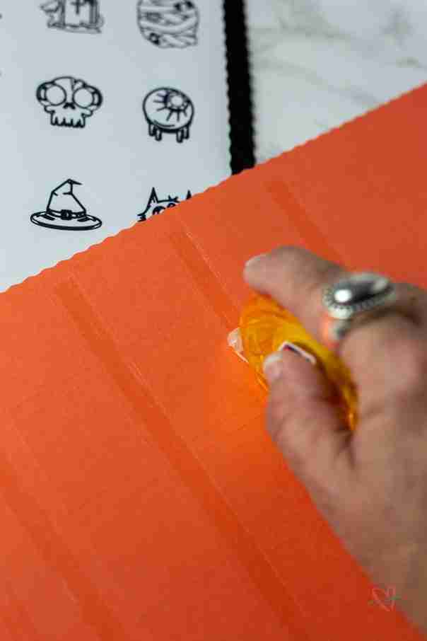Putting tape between boxes on orange paper