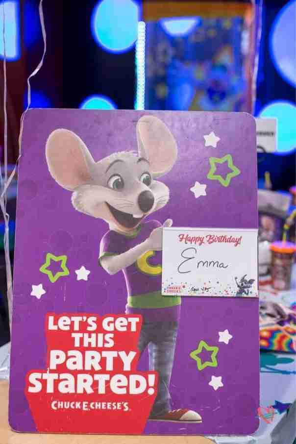 Chuck E. Cheese birthday party sign on table