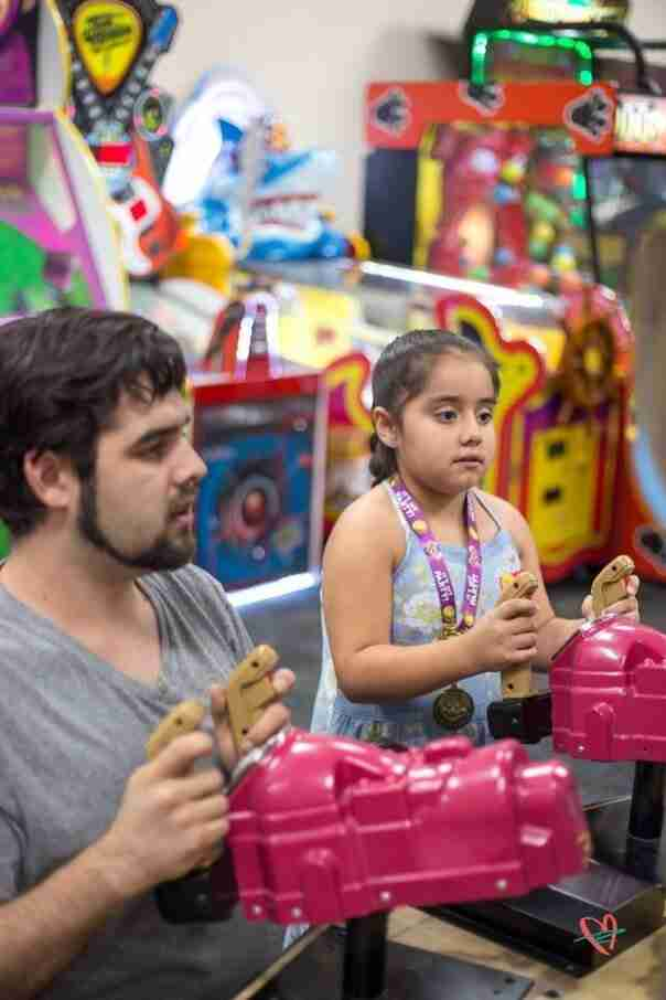 Dad and daughter playing game at Chuck E. Cheese birthday party