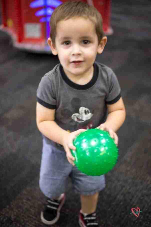Boy holding green ball at Chuck E. Cheese