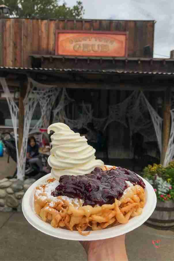 Boysenberry funnel cake in front of Knott's Berry Farm Ghost Town Grill