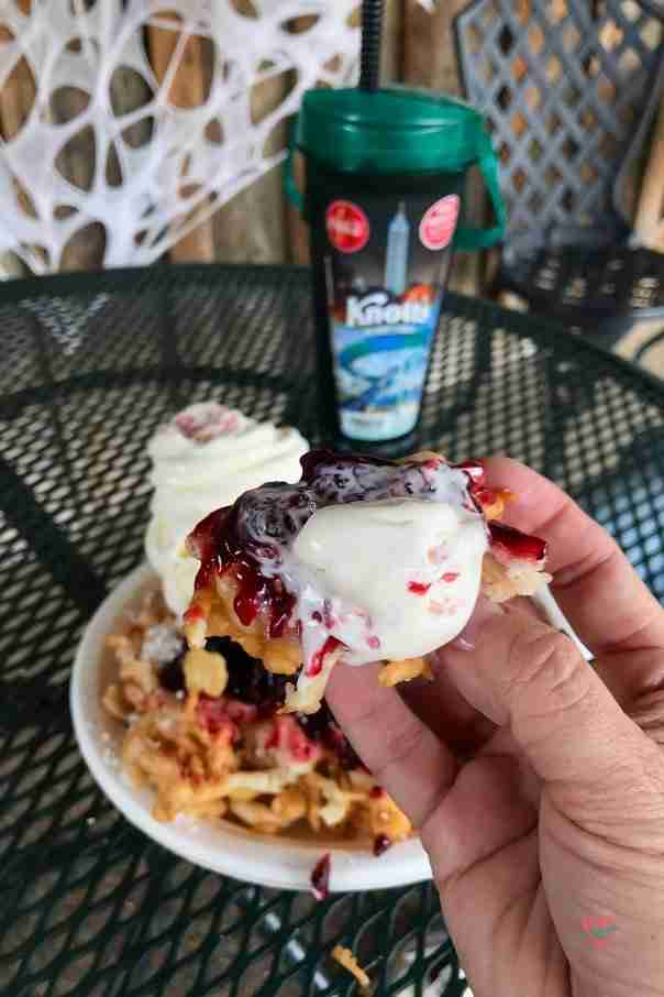 Hand holding a bite of boysenberry funnel cake at a table