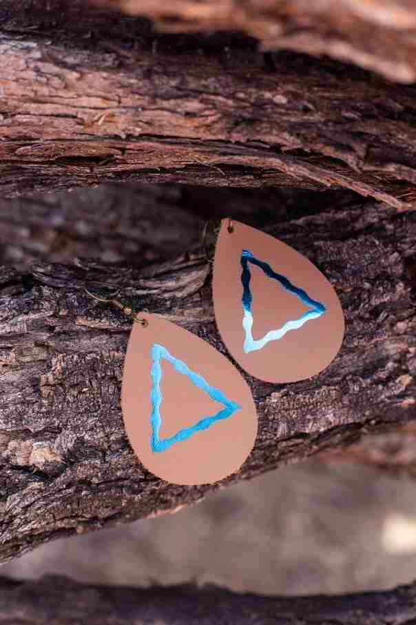 DIY leather earrings on log of wood